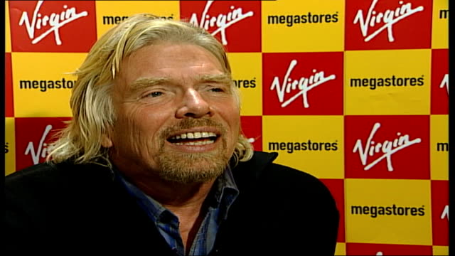Sir Richard Branson condemns Murdoch shares purchase Manchester Virgin Megastore Richard Branson seated on sofa hands mobile phone back to unseen...