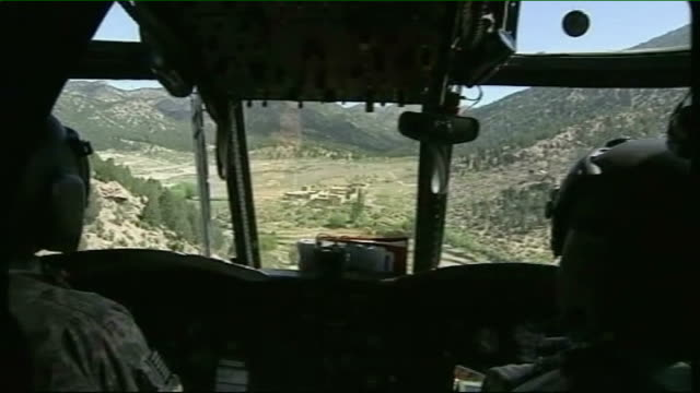 Implications for Karzai Helmand Province NATO soldier manning machine gun mounted in helicopter View from cockpit of helicopter as along EXT US...
