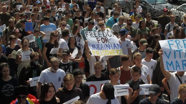 relatives and activists carry placards with names and photos of ukrainians which were captured and sentenced by russia during march called 'freedom... - verurteilung stock-videos und b-roll-filmmaterial