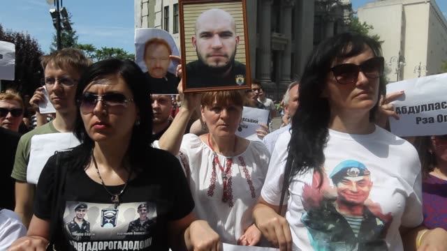 relatives and activists hold placards with names and photos of ukrainians which were captured and sentenced by russia during march called 'freedom to... - verurteilung stock-videos und b-roll-filmmaterial