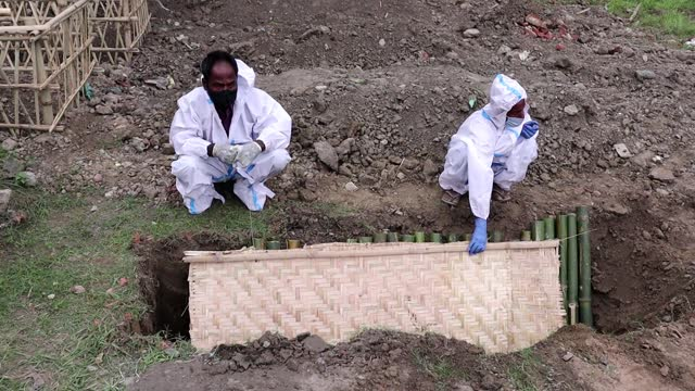 relatives and municipal workers in protective suit bury the body of a person, who died of the covid-19 coronavirus disease, at a burial ground on may... - indian politics stock videos & royalty-free footage