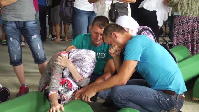 relatives mourn after coffins of the 71 victims of 1995 srebrenica genocide arrived in potocari village of srebrenica bosnia and herzegovina on july... - srebrenica stock videos and b-roll footage