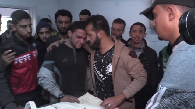 relatives mourn as the body of 20yearold palestinian musab hous who was killed in israeli raids is brought to the morgue of alshifa hospital in gaza... - gaza strip stock videos & royalty-free footage