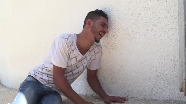 relatives mourn over the body of sabri ahmed abu khader at a hospital in gaza city after he was killed by israeli fire near the gaza strip's border... - gaza city stock videos & royalty-free footage