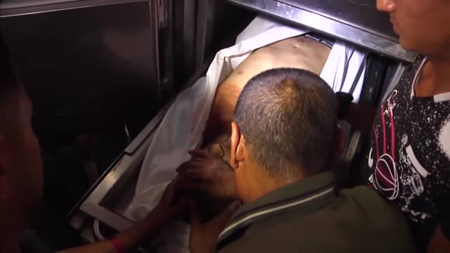 Relatives of two Palestinians who were martyred by Israeli gunfire during antioccupation rallies in the Gaza Strip mourn over their bodies at the...