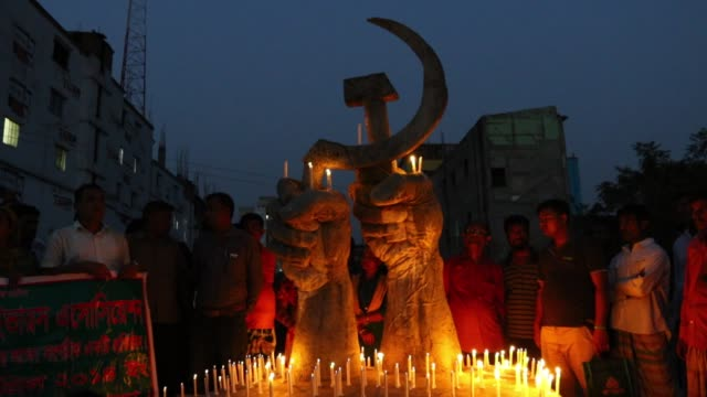 relatives of victims of the rana plaza collapse in bangladesh hold candles in front of a monument for victims of the rana plaza factory on april 23... - garment stock videos & royalty-free footage