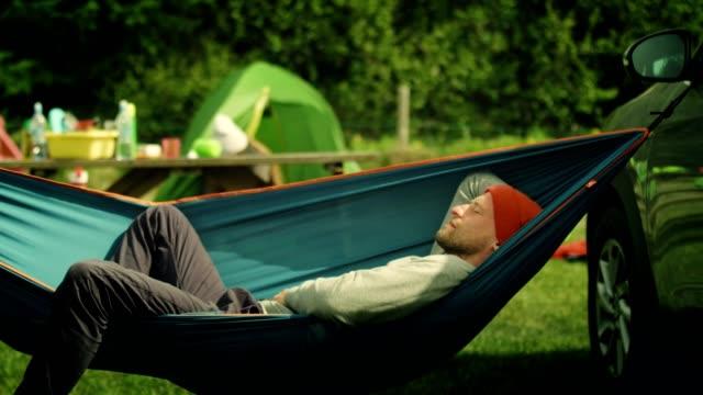 entspannen sie in der hängematte. camping - hängematte stock-videos und b-roll-filmmaterial