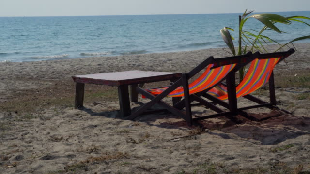 relax on the beach under palm trees in the tropics - beach chairs stock videos & royalty-free footage