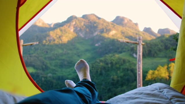 relax woman lying down and cross leg on blanket in tent and looking at mountain view in sunset time at camping vacation holiday - tenda da campeggio video stock e b–roll