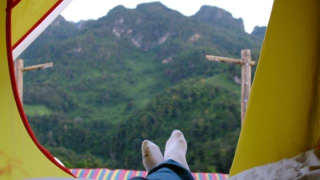 vidéos et rushes de détendez la femme couchée et traversez la jambe sur la couverture dans la tente et regardant la vue de montagne dans l'heure du coucher du soleil au camping vacances de vacances - randonnée pédestre