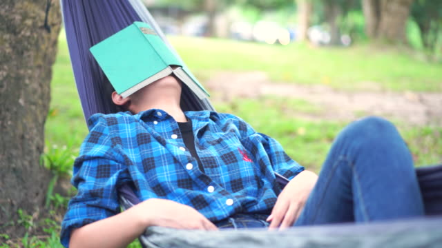 relax young woman sleeping with a book in a swinging hammock at campground - 仰向きに寝る点の映像素材/bロール