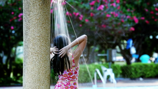 Relaxation Asia girl teen in out-door shower on swimming pool.