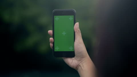 relaxation in park : smart phone green screen - human hand stock videos & royalty-free footage