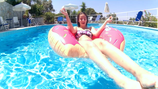 Relaxation on inflatable ring in swimming pool