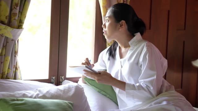 Relaxation time, Asian woman plannig on notebook for plan to travel and talking on phone on bed.