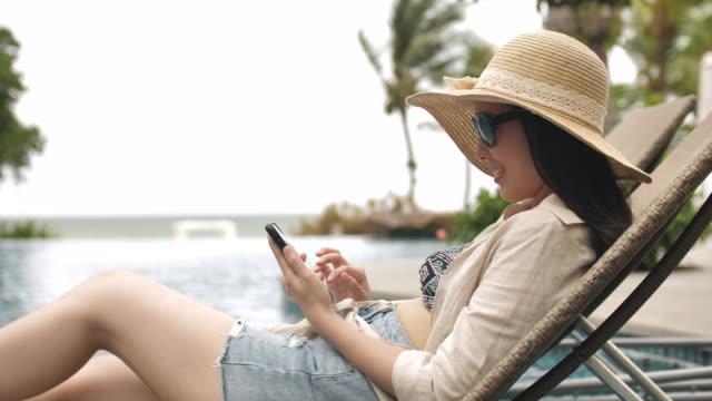 stockvideo's en b-roll-footage met ontspannen aziatische jonge vrouw kijken naar mobiele telefoon in het zwembad resort - buitenbad