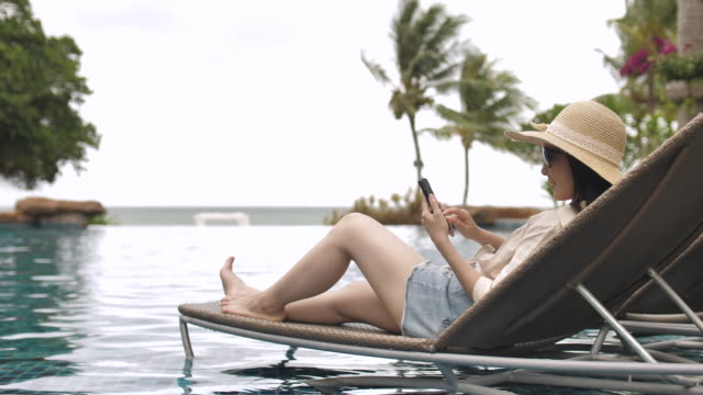relaxed asian young woman looking at mobile phone in resort swimming pool - lido stock videos & royalty-free footage