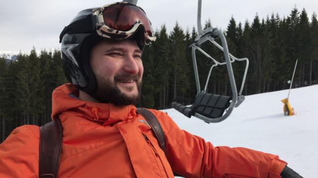 stockvideo's en b-roll-footage met ontspannen bebaarde man bewondert het panorama met ski-pistes zittend op skilift - skilift