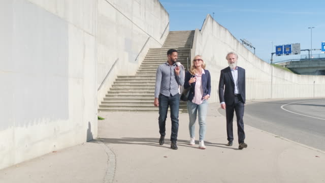 relaxed business colleagues walking together - concrete wall stock videos & royalty-free footage