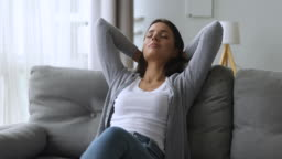 Relaxed calm beautiful girl leaning on sofa dreaming enjoying wellbeing
