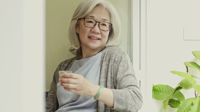"relaxed chinese senior woman enjoying tea at cafe - xavierarnau or ""xavier arnau serrat"" stock videos & royalty-free footage"