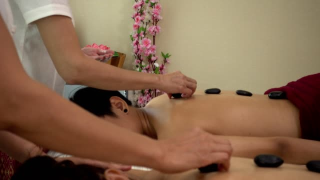 relaxed couple having hot stone massage - lastone therapy stock videos & royalty-free footage