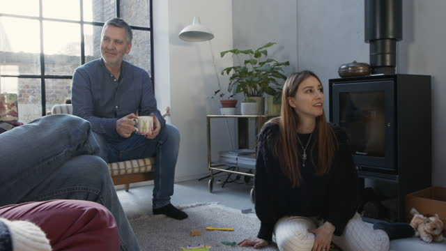 relaxed family in living room drinking coffee - multi generation family stock videos & royalty-free footage