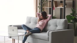 Relaxed girl resting sit on sofa enjoy stress free day