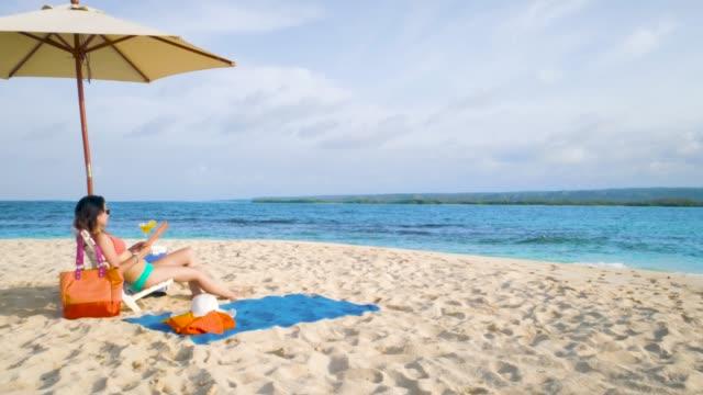 stockvideo's en b-roll-footage met ontspannen hispanic jonge vrouw zit en zonnebaden op het strand van een tropische turquoise caraïbische cay - zonnescherm gefabriceerd object