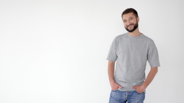 Relaxed man in casual clothes holding hands in pockets then folded arms