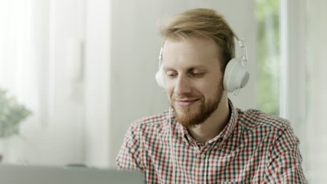 relaxed man using laptop and headphones in modern office - e learning stock videos & royalty-free footage