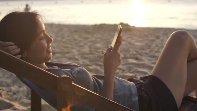 avslappnad blandad race ung kvinna titta på mobil telefon i hängmatta på stranden nära havet vid solnedgången - solstol bildbanksvideor och videomaterial från bakom kulisserna