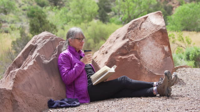 relaxed outdoor enthusiast drinking coffee and reading book in sandstone canyon - letteratura video stock e b–roll