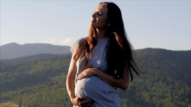 vídeos y material grabado en eventos de stock de relajado mujer embarazada tocar su vientre - abdominales