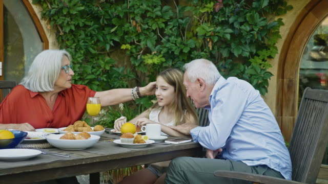 relaxed senior couple having breakfast with granddaughter - things that go together stock videos & royalty-free footage