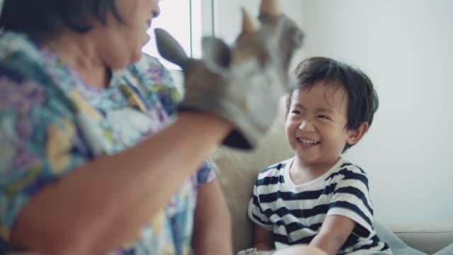 entspannt senior parenting. asiatische seniorin und enkel spielen spielzeug - charakterkopf stock-videos und b-roll-filmmaterial