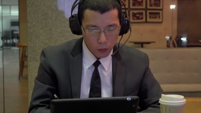 vídeos de stock, filmes e b-roll de cara de terno relaxado em fones de ouvido ouvindo música e trabalhando em seu tablet - vestuário de trabalho formal