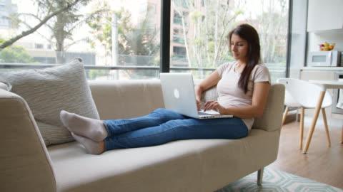 stockvideo's en b-roll-footage met ontspannen vrouw thuis gebruikend haar sociale media op laptop terwijl het liggen op laag - online winkelen