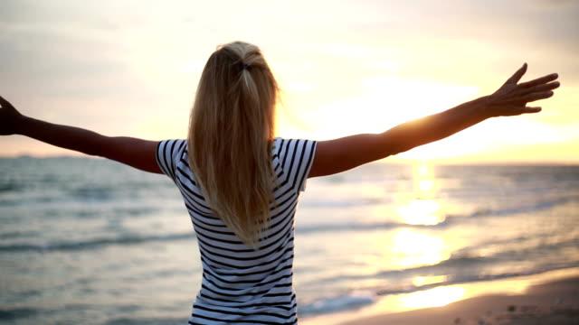 vídeos de stock, filmes e b-roll de mulher relaxada respirar ar fresco aumento de armas ao pôr do sol - braço humano