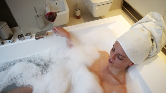 relaxed woman drinking wine in bathtub - bubble bath stock videos and b-roll footage