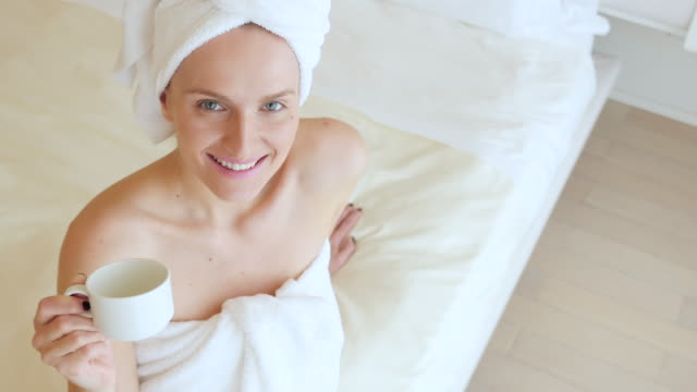 relaxed woman holding cup of tea - wrapped in a towel stock videos & royalty-free footage