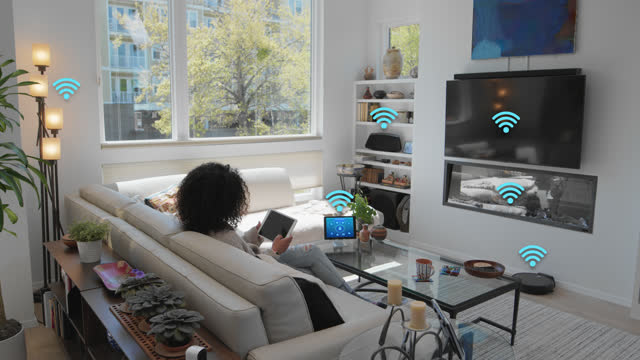 relaxed woman sits on her couch and connects her tablet to other smart devices - internet of things stock videos & royalty-free footage