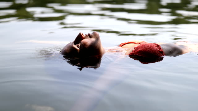 relaxed young female floating in lake - floating on water stock videos & royalty-free footage