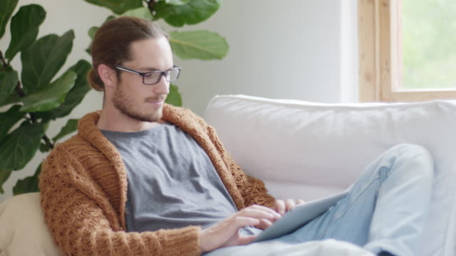relaxed young man typing on digital tablet at home - houseplant stock videos and b-roll footage