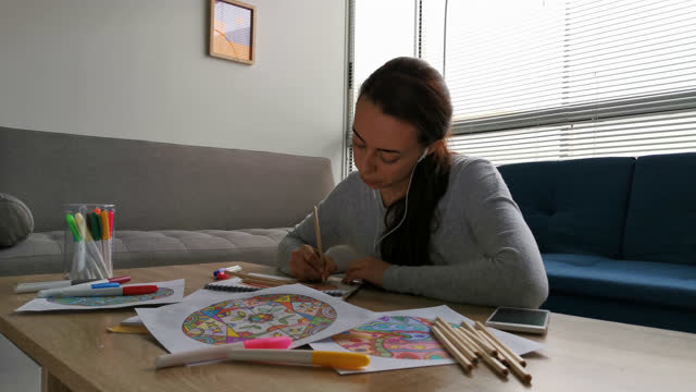 relaxed young woman at home during covid-19 lockdown coloring mandalas while listening music with headphones - mental wellbeing stock videos & royalty-free footage