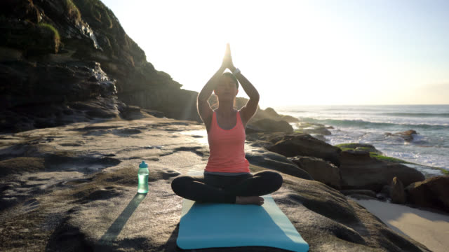 relaxed young woman practicing yoga next to the beach - balance life stock videos and b-roll footage