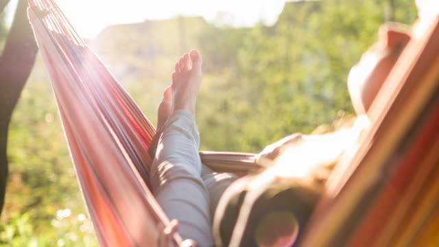 vídeos de stock e filmes b-roll de relaxing and daydreaming in a hammock in springtime - acampar