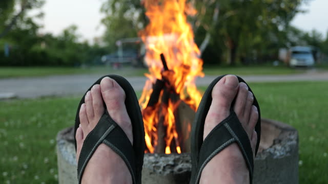 relaxing by the bonfire in camping in summer - piedi alzati video stock e b–roll