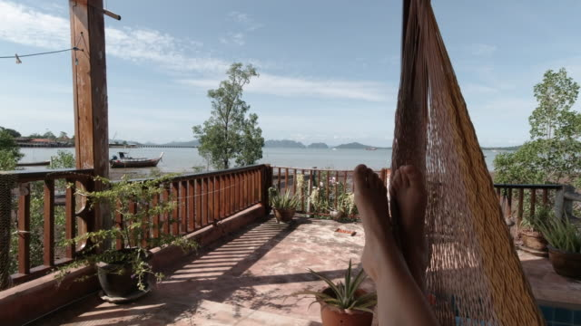 relaxing in a hammock on vacation first person point of view - feet up stock videos & royalty-free footage