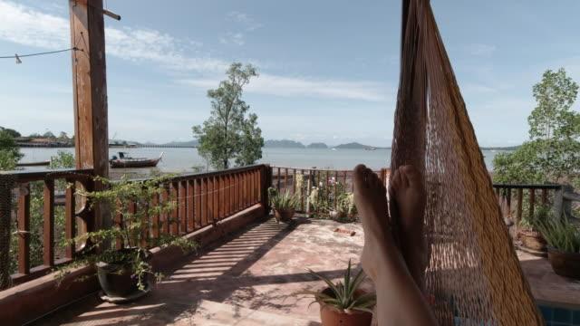 vídeos de stock, filmes e b-roll de relaxamento em um hammock no ponto da primeira pessoa das férias da vista - de pé para cima